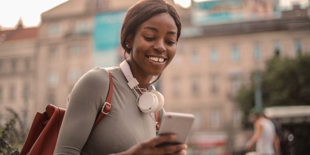 woman smiling and looking at her phone with a backpack on