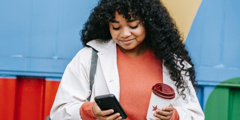 woman texting on her phone and holding a coffee cup